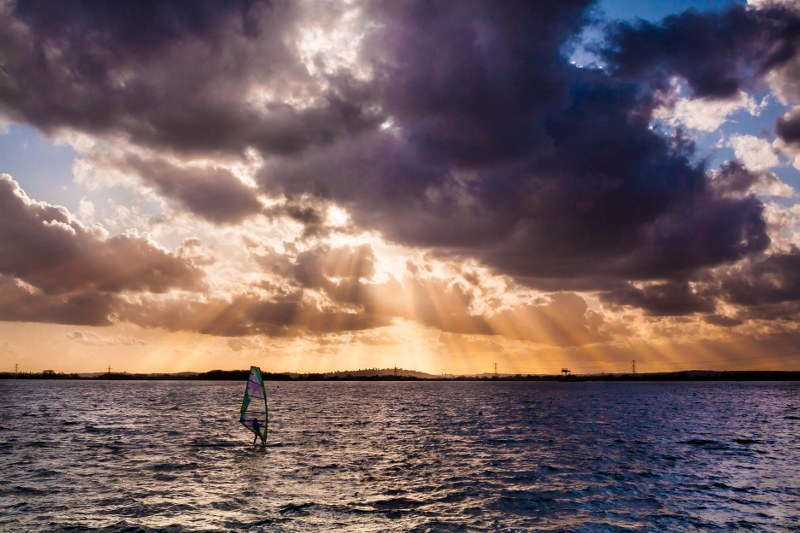 This photo always stirs up something in me. It was taken in early March at the Queenmary Windsurfing Club near London when the water and wind has hardly begun to warm up from the winter freeze. It takes the most dedicated windsurfer to be out at this time. I had just got off the water and was trying to get the blood back to my fingers when I saw this lone sailor using the little daylight left to get their fix.